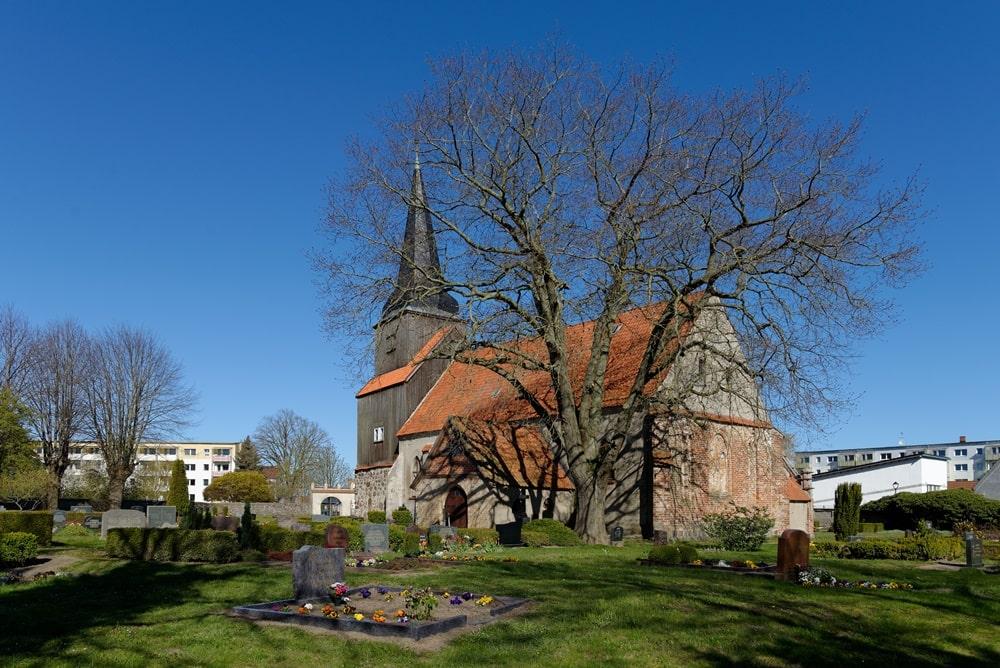 Kirchhof der evangelischen Kirche in Krien mit Blick auf das Priesterportal