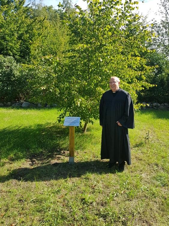 Prädikant Burkhard Fröhlich vor dem Lindenbaum und der Gedenktafel