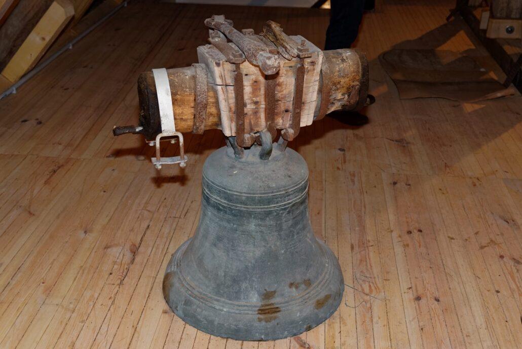 Die noch untätige Glocke in der Kirche in Wegezin neben dem Glockenstuhl